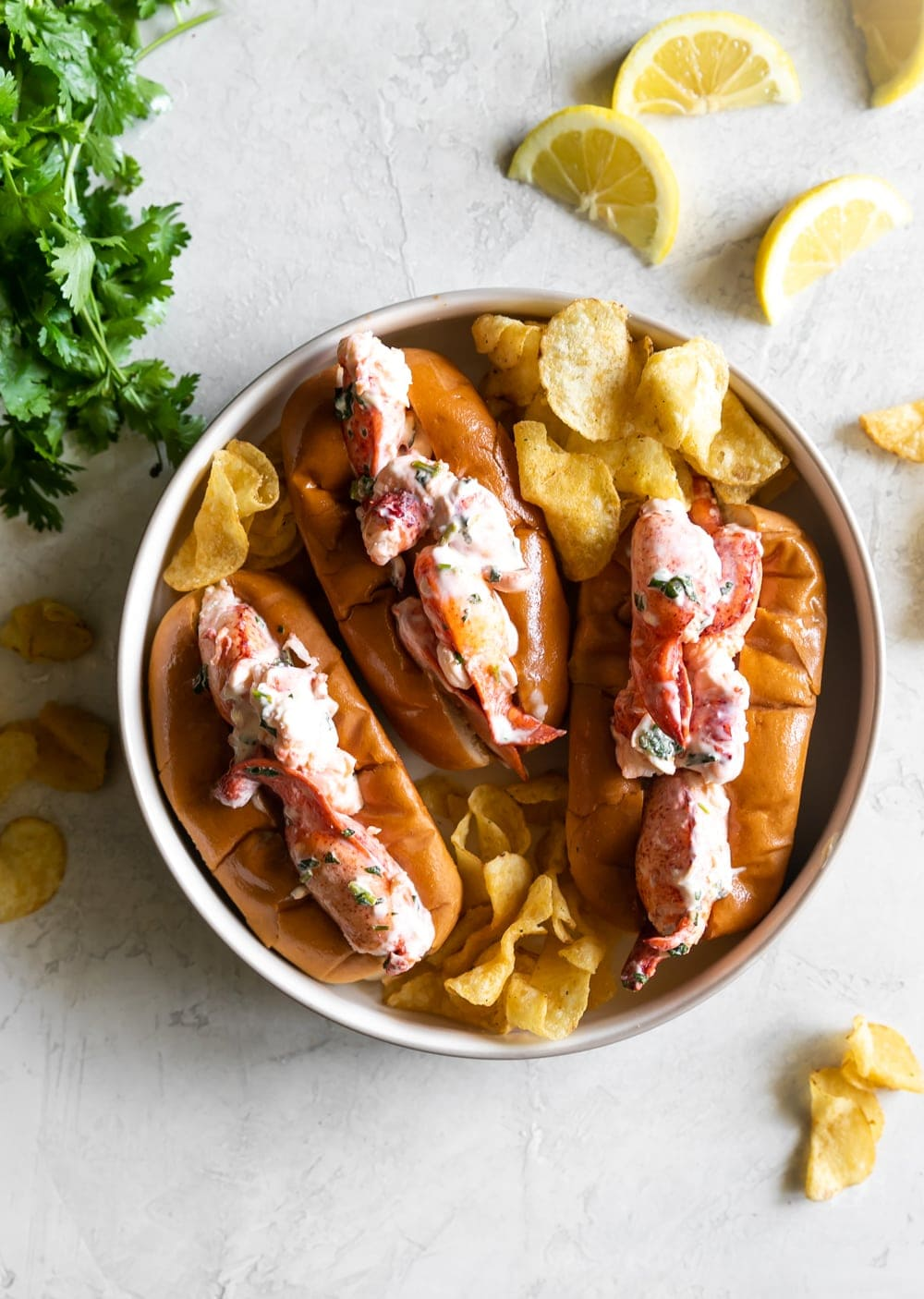top view of maine lobster rolls with kettle cooked chips and lemon slices on buttered toasted buns