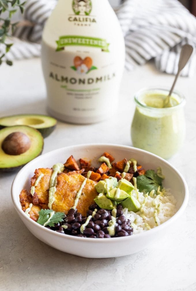 A hearty vegan Cuban bowl made with rice, sweet potatoes, black beans, tostones (plantains) and dairy-free, creamy avocado ranch dressing!