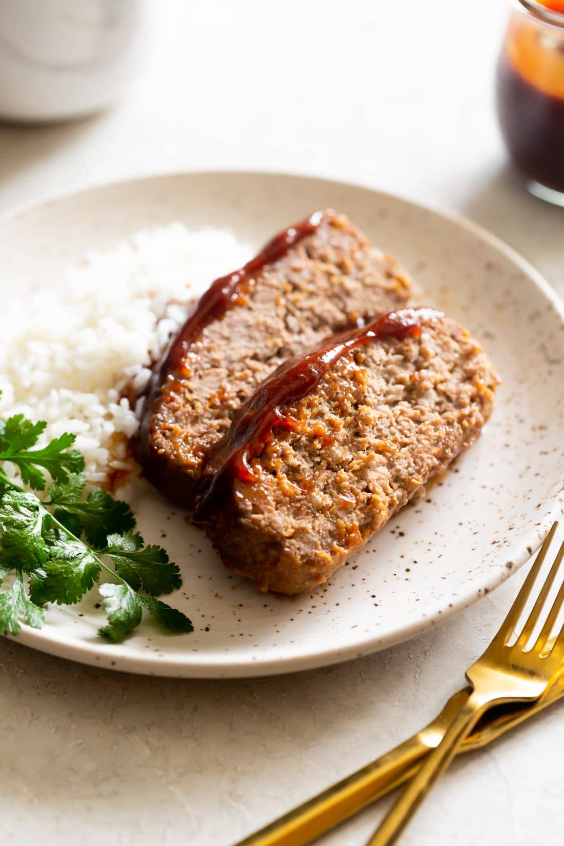 sliced meatloaf with guava bbq sauce served with white rice on a speckled plate