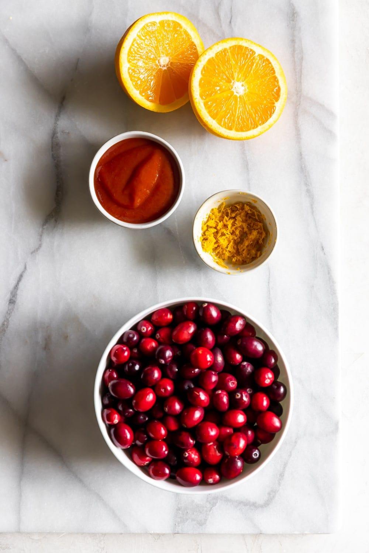 sliced oranges, orange zest, fresh cranberries, guava marmalade on a marble board