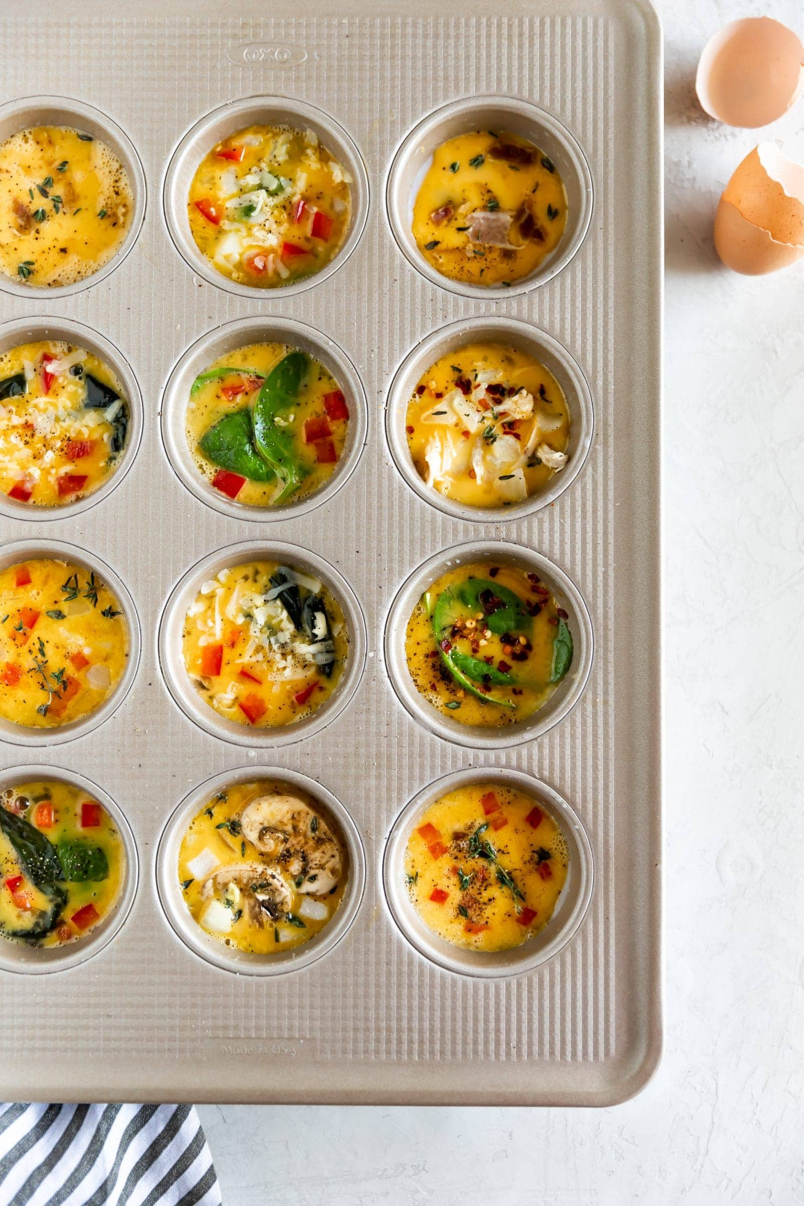 Egg muffin cups in muffin tin, ready to bake