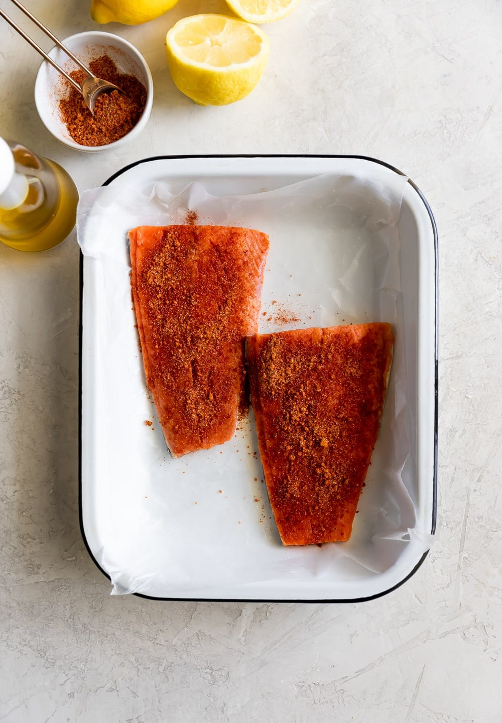 salmon on tray being seasoned with spices