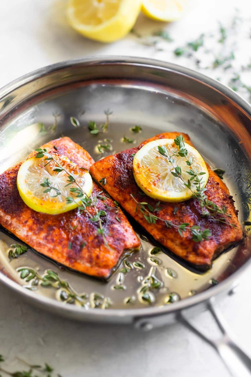 pan seared salmon on skillet with lemon slices