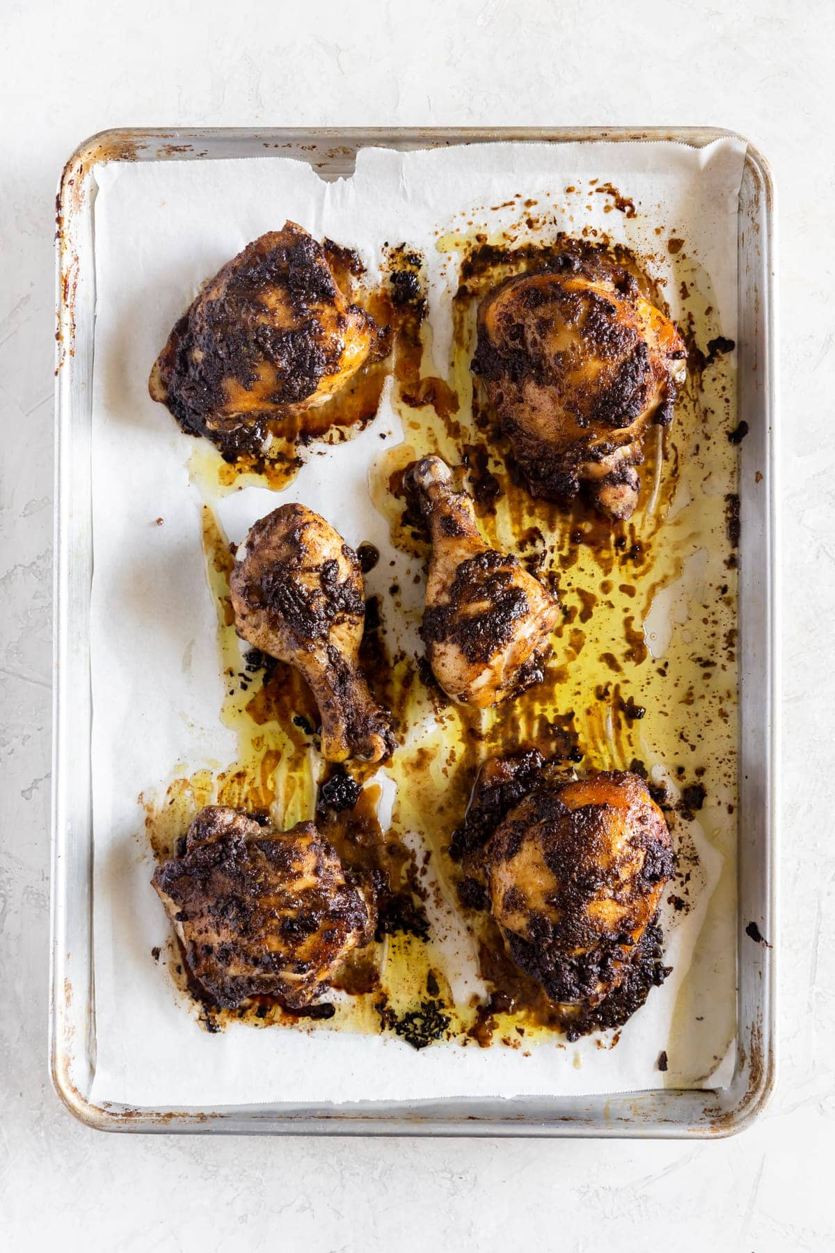 chicken cooked with jerk marinade on a baking sheet right out of the oven