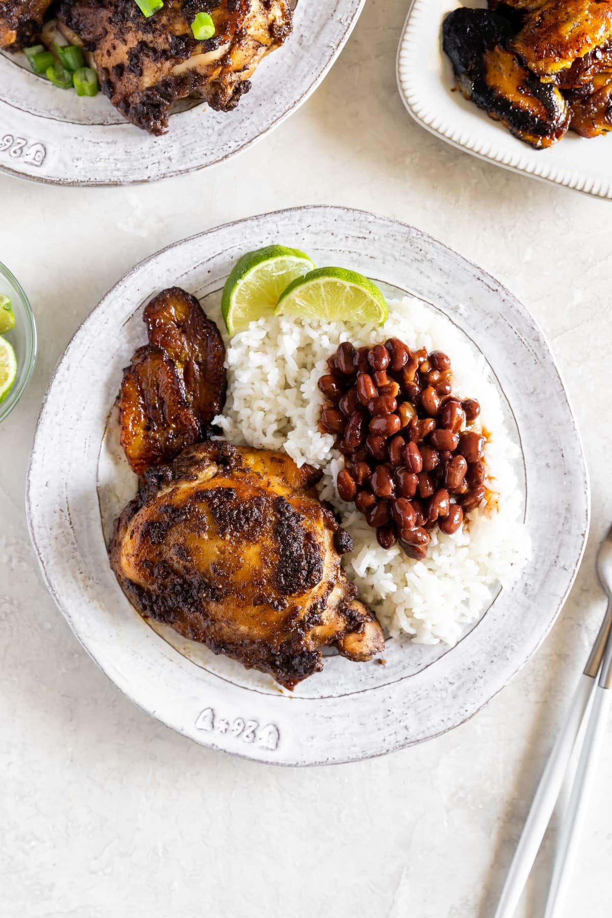 jerk chicken on a white plate with rice, beans, and sweet plantains