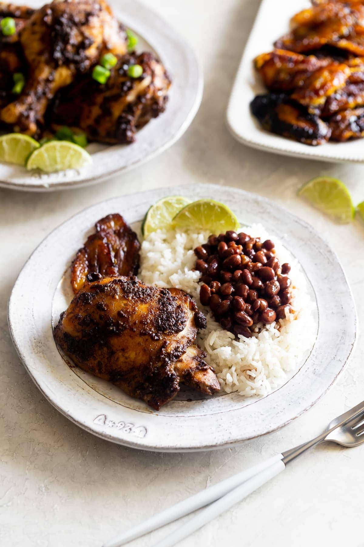 jerk chicken with a side of white rice, black beans, sweet plantains, and lime wedges on a white plate