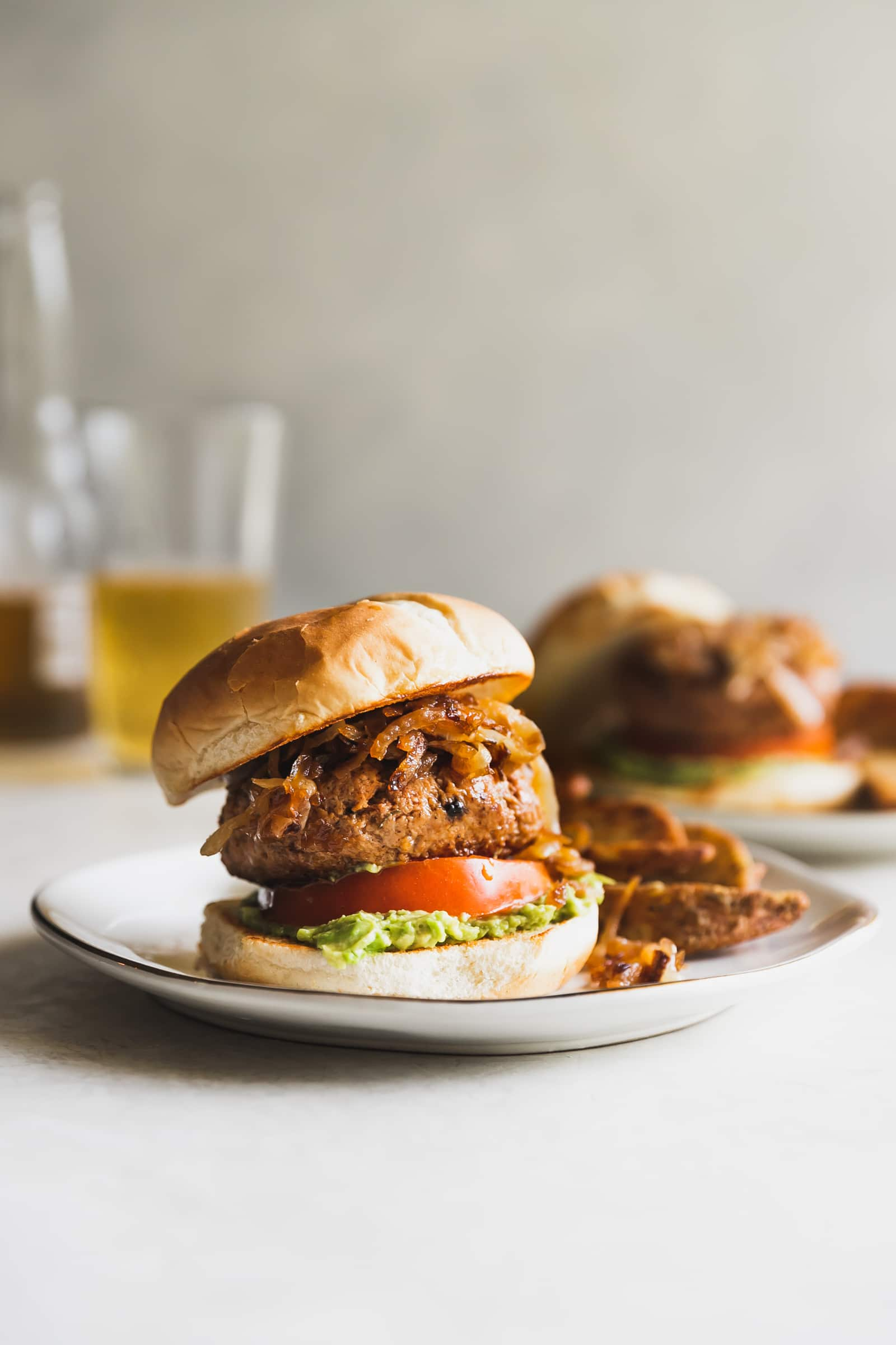 Tender, flavorful juicy turkey burgers made with the best seasoning then topped with mashed avocado, tomato and caramelized onions.