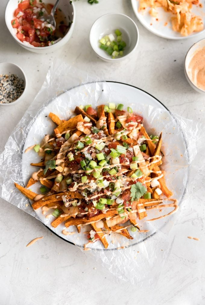 The best kimchi fries! Crispy baked sweet potato fries topped with kimchi, pico de gallo, green onions, everything bagel seasoning, cilantro and spicy mayo.