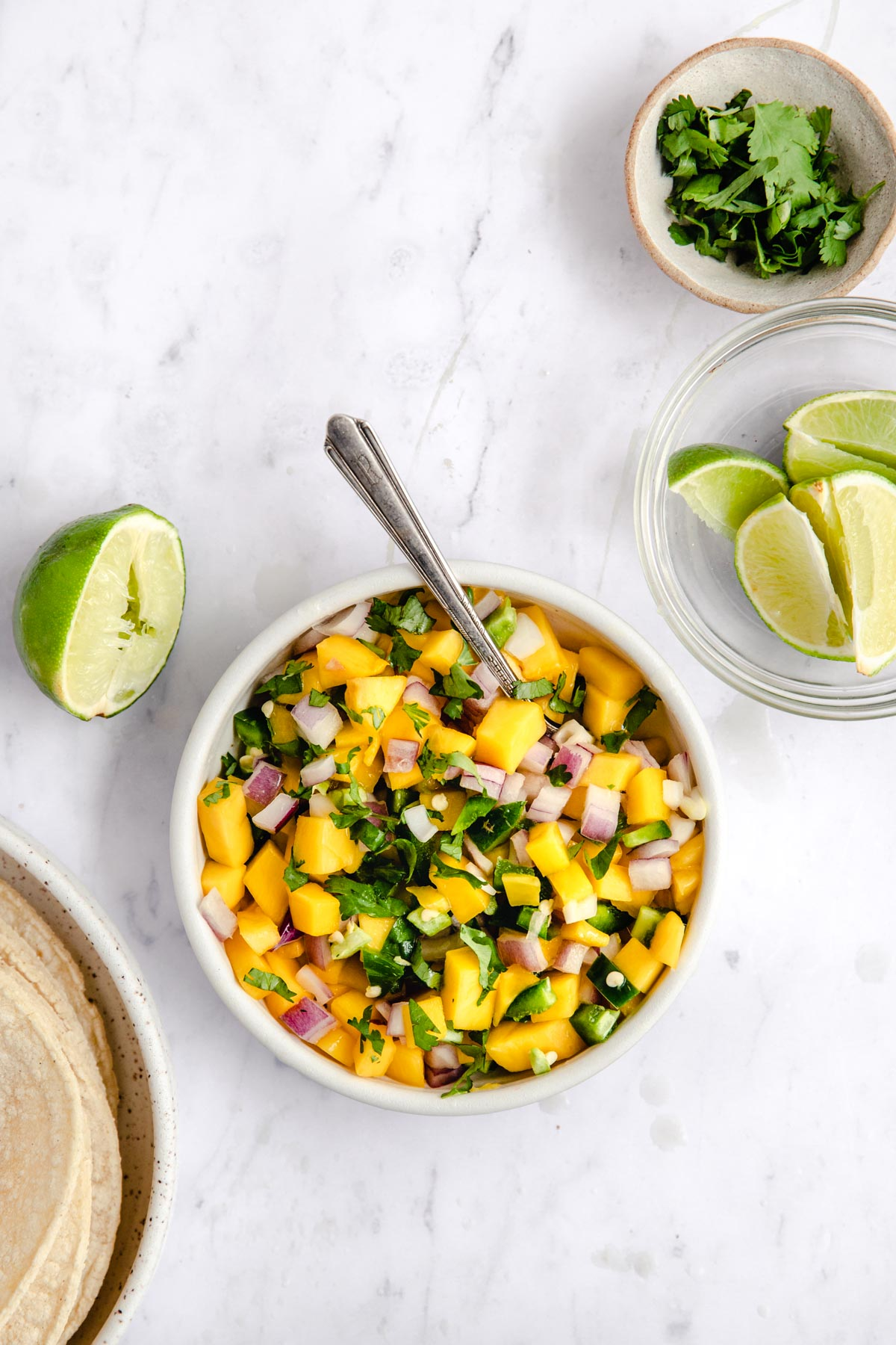 bowl with mango salsa on a white table with cilantro and lime wedges