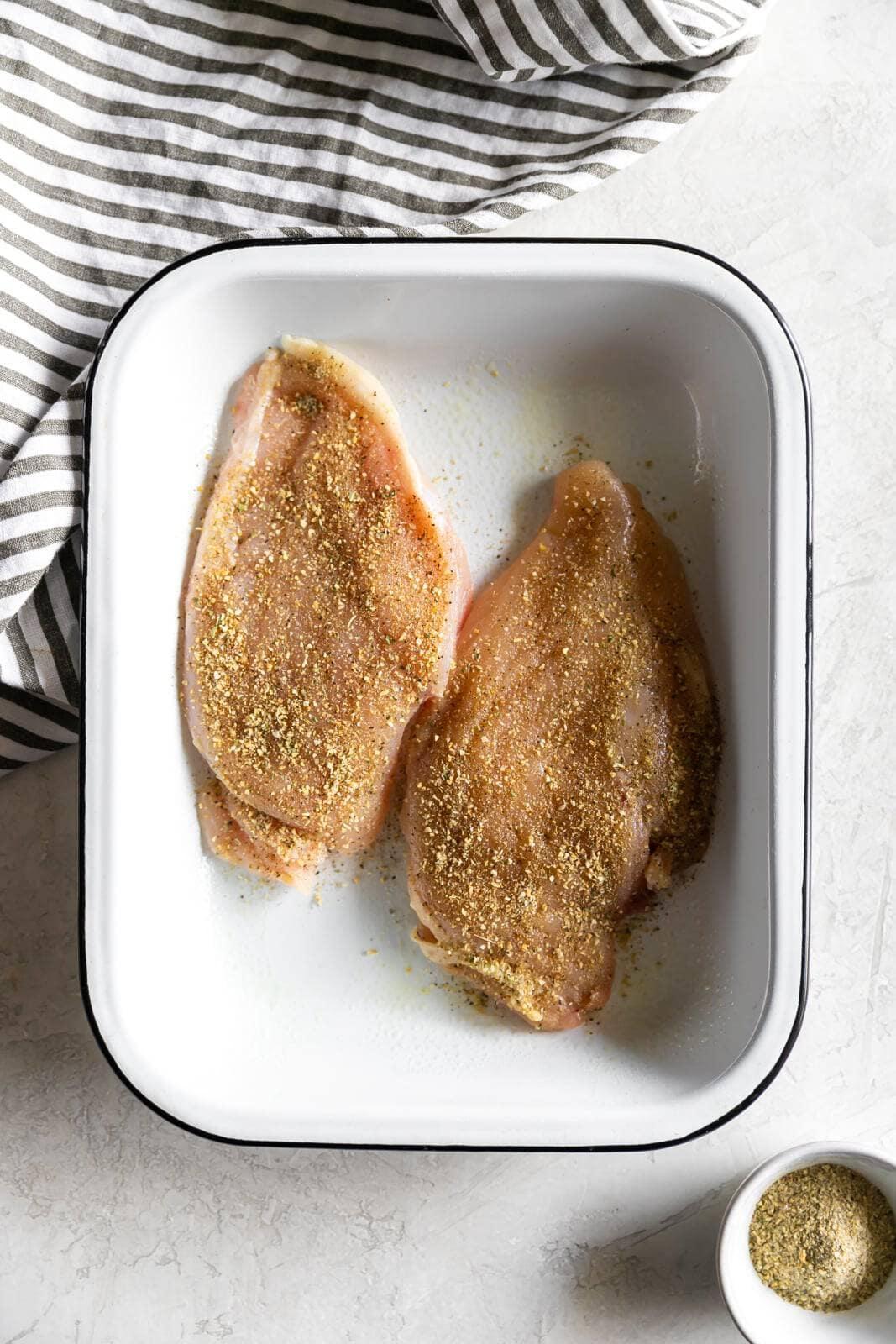 Two seasoned chicken breasts inside cooking pan