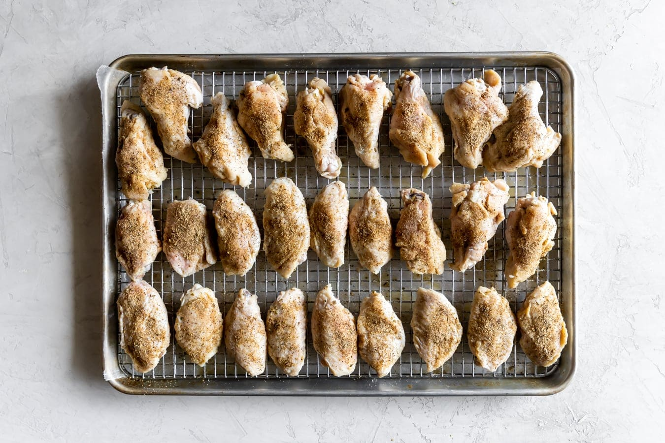 chicken wings on a wire rack on a baking sheet before baking in the oven