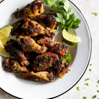 citrus and garlic marinated chicken wings on a plate with lime and cilantro