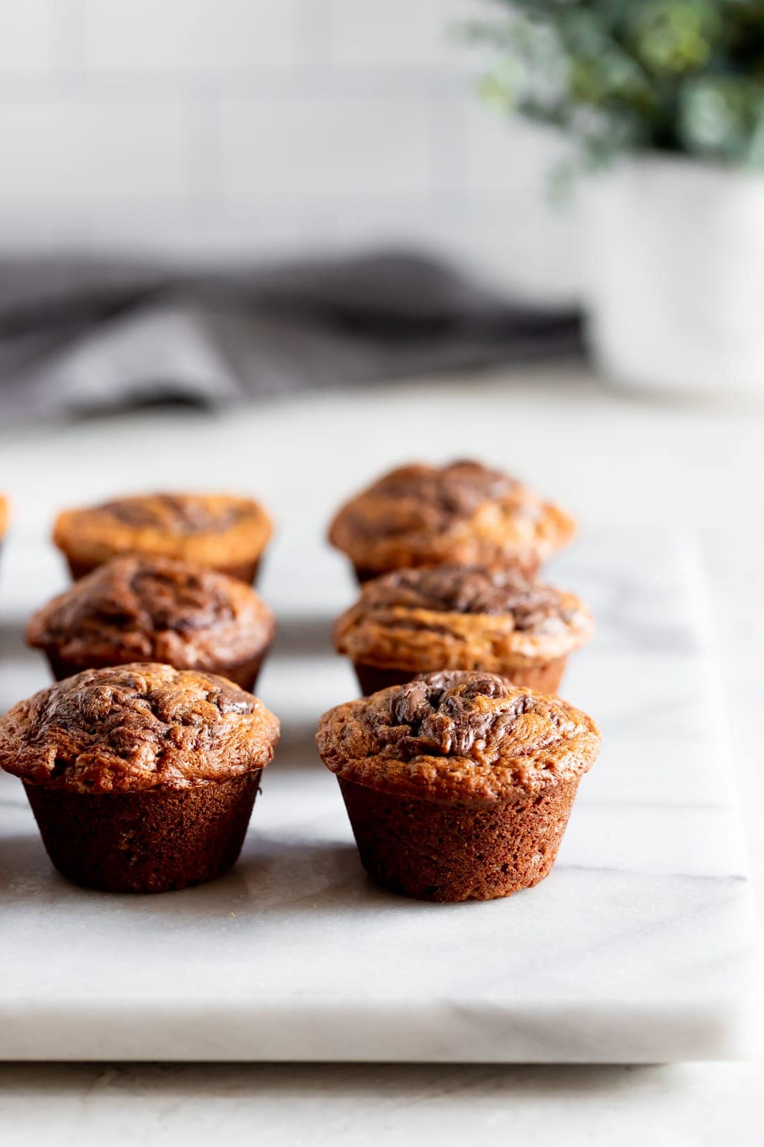 moist banana muffins swirled with nutella on a marble slab