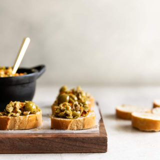 A simple yet irresistible appetizer made with tart, briny olives, capers, fresh garlic, pepper, and olive oil then served on toasted baguette slices brushed with olive oil.