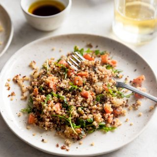 Salmon served with quinoa, tomatoes, onions, and arugula