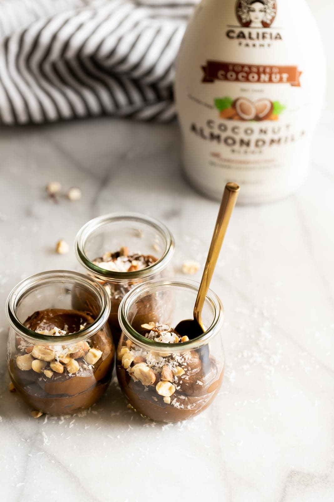A creamy dairy-free avocado chocolate mousse made with just 5 ingredients then topped with coconut flakes and chopped hazelnuts!