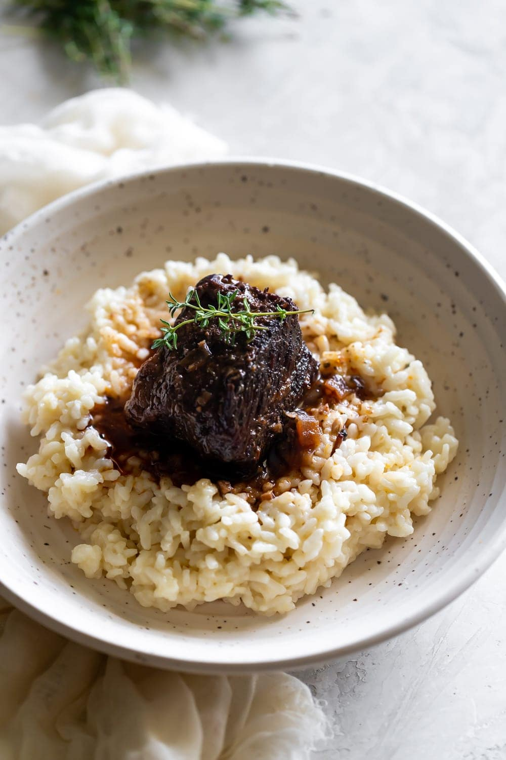 red wine braised short ribs on top of Parmesan risotto in a ceramic bowl with thyme