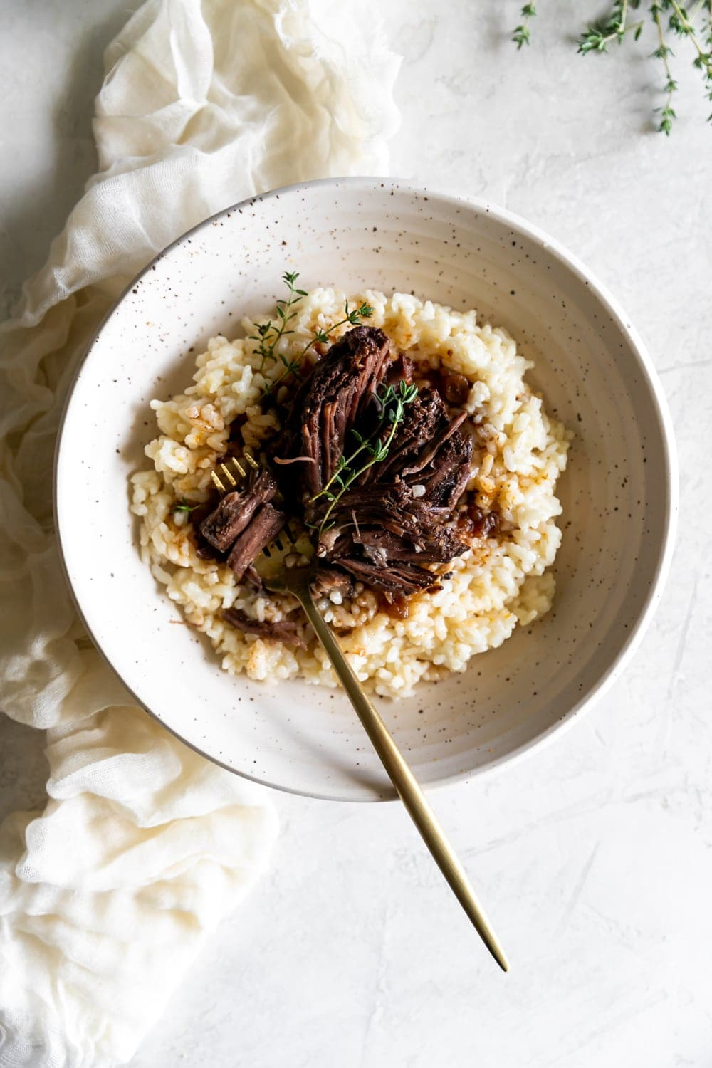 red wine braised short ribs on top of risotto with a gold folk in a ceramic bowl