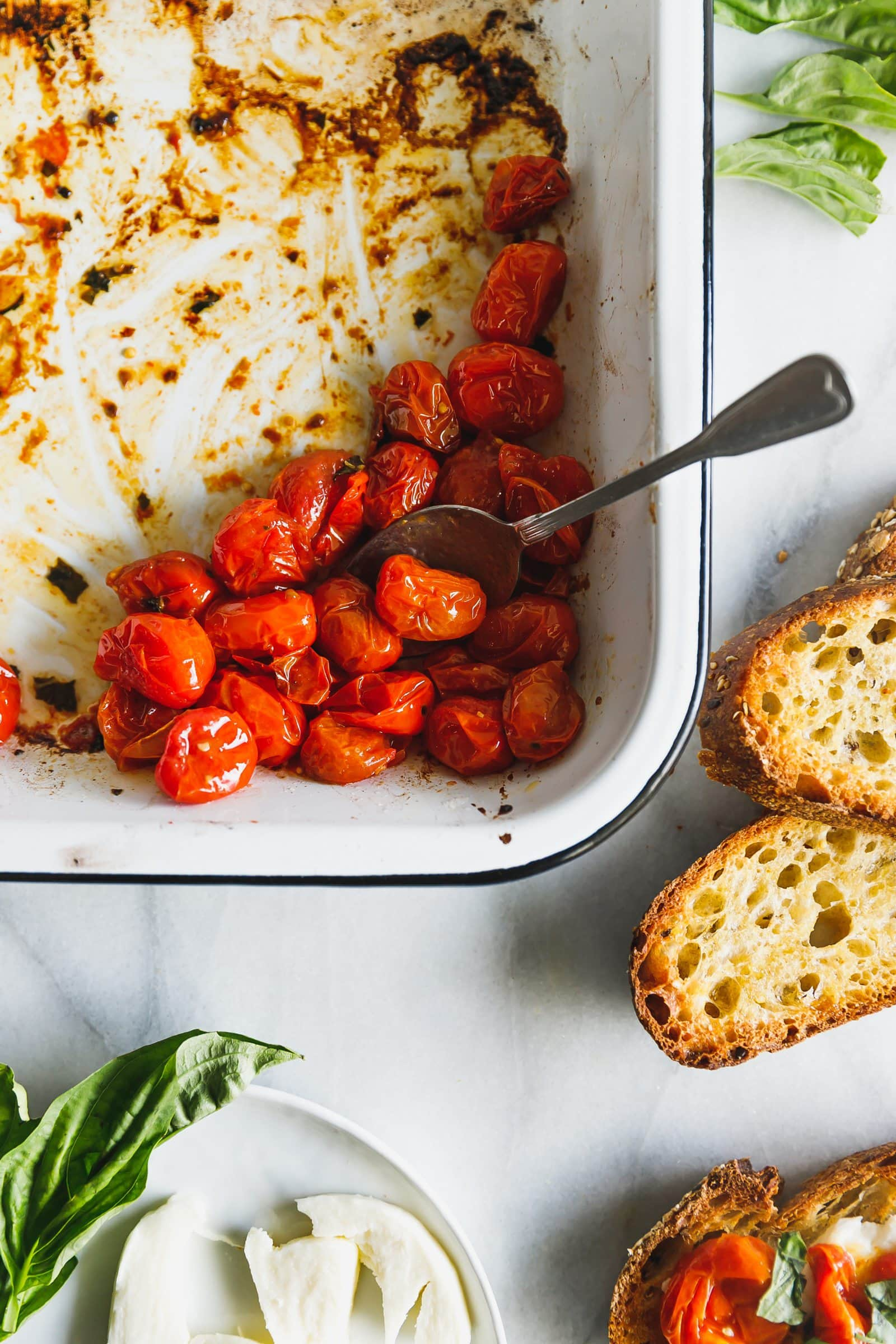Caprese salad on toast! Cherry tomatoes are roasted until bursting and lightly browned then served with fresh mozzarella on thick, olive-oil-toasted bread.
