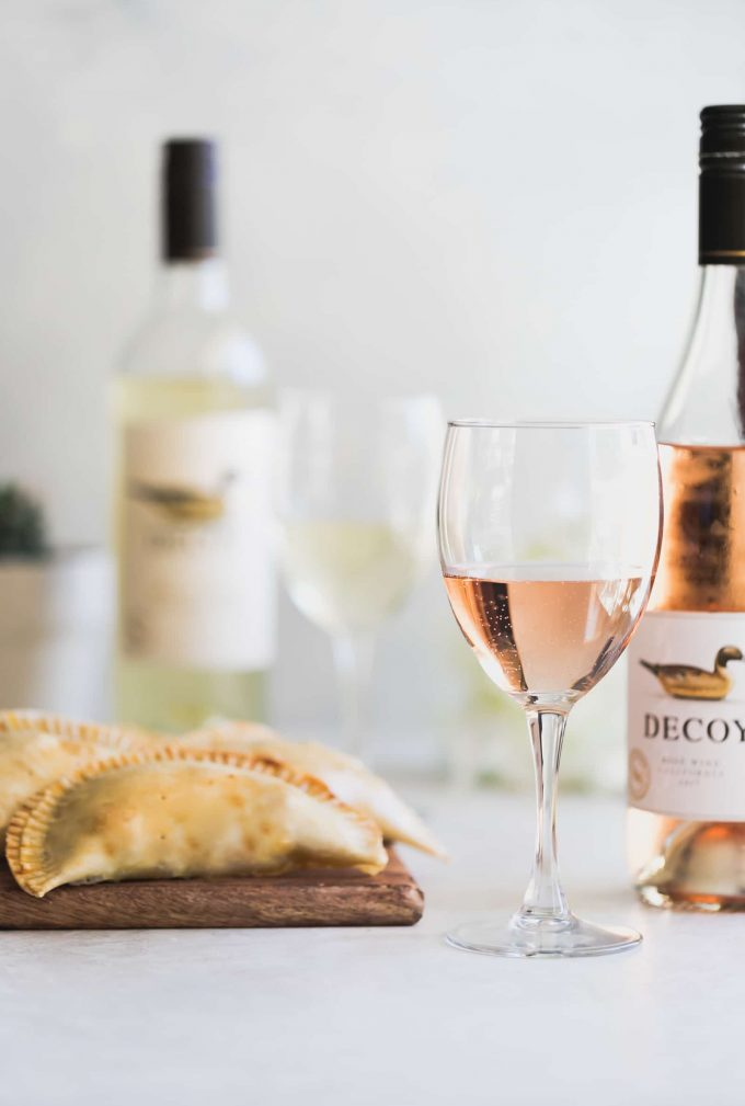 Two delicious types of baked savory sweet empanadas (dates, bacon & brie and mushroom, caramelized onions, & goat cheese) are the perfect pairing for rosé and white wine!