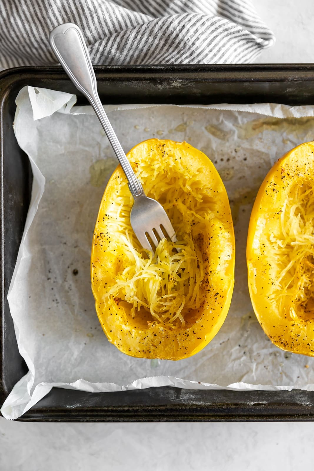A spaghetti squash cut lengthwise on a baking dish with a fork shredded into spaghetti