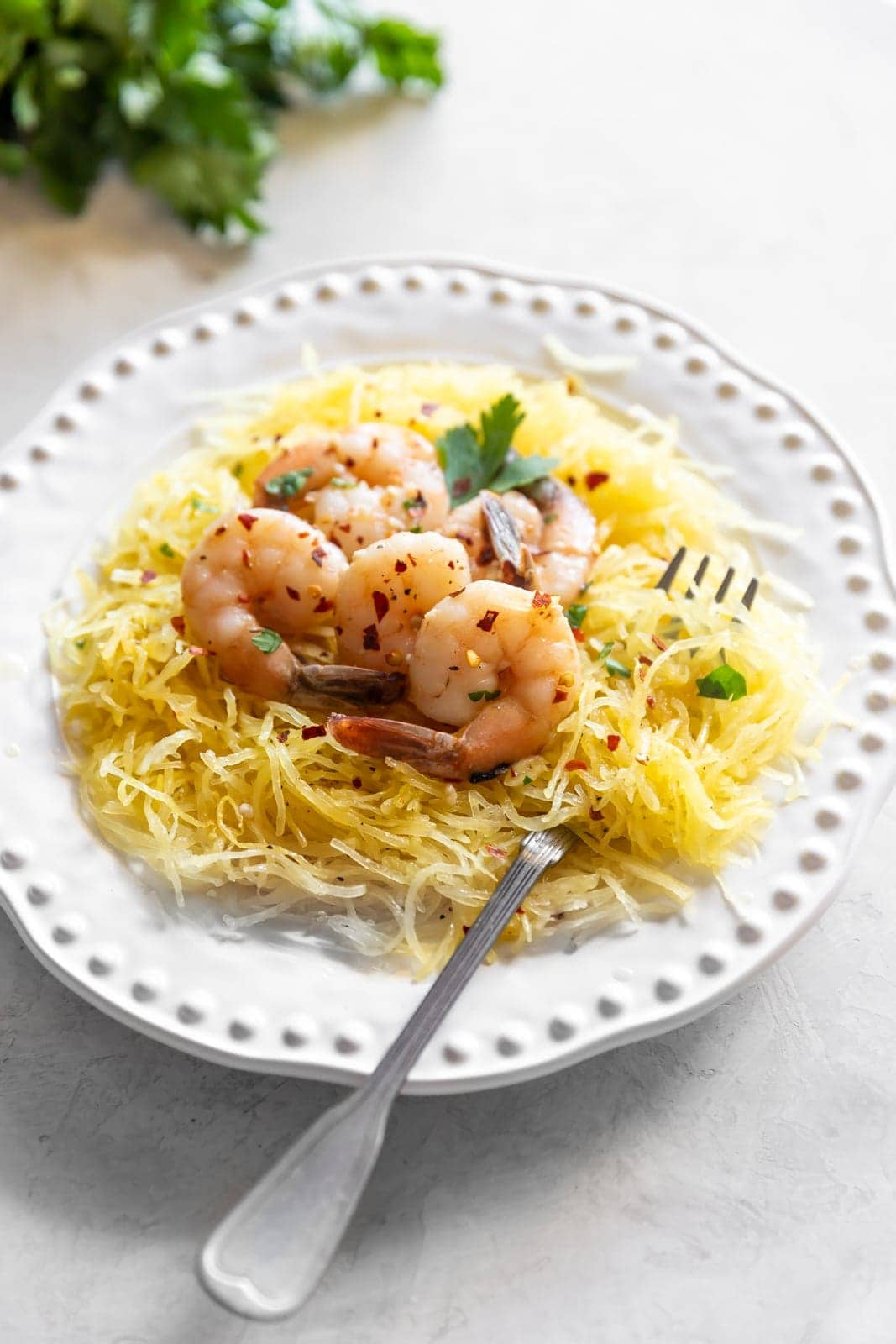 Sautéed shrimp tossed in a quick + easy garlic, red pepper flakes, parsley, white wine, and butter sauce served on top of spaghetti squash.