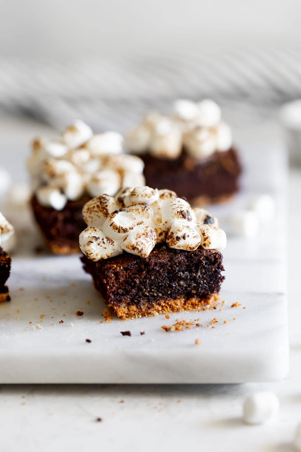 smores brownies on a marble slab with toasted marshmallows
