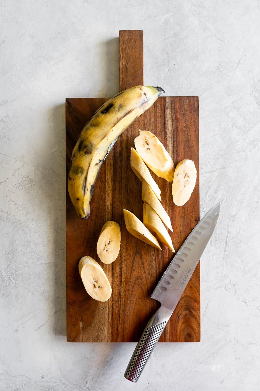ripe plantain being sliced diagonally for maduros