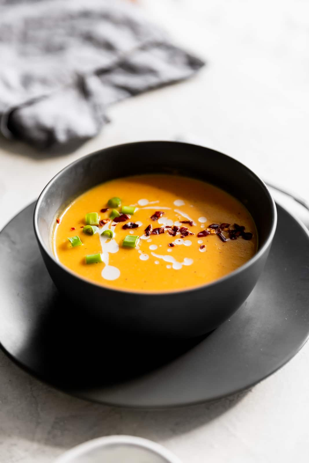 Creamy, dairy-free, and spicy vegan Thai butternut squash soup made with fresh ginger, red curry paste and coconut milk. Ready in 25 minutes!