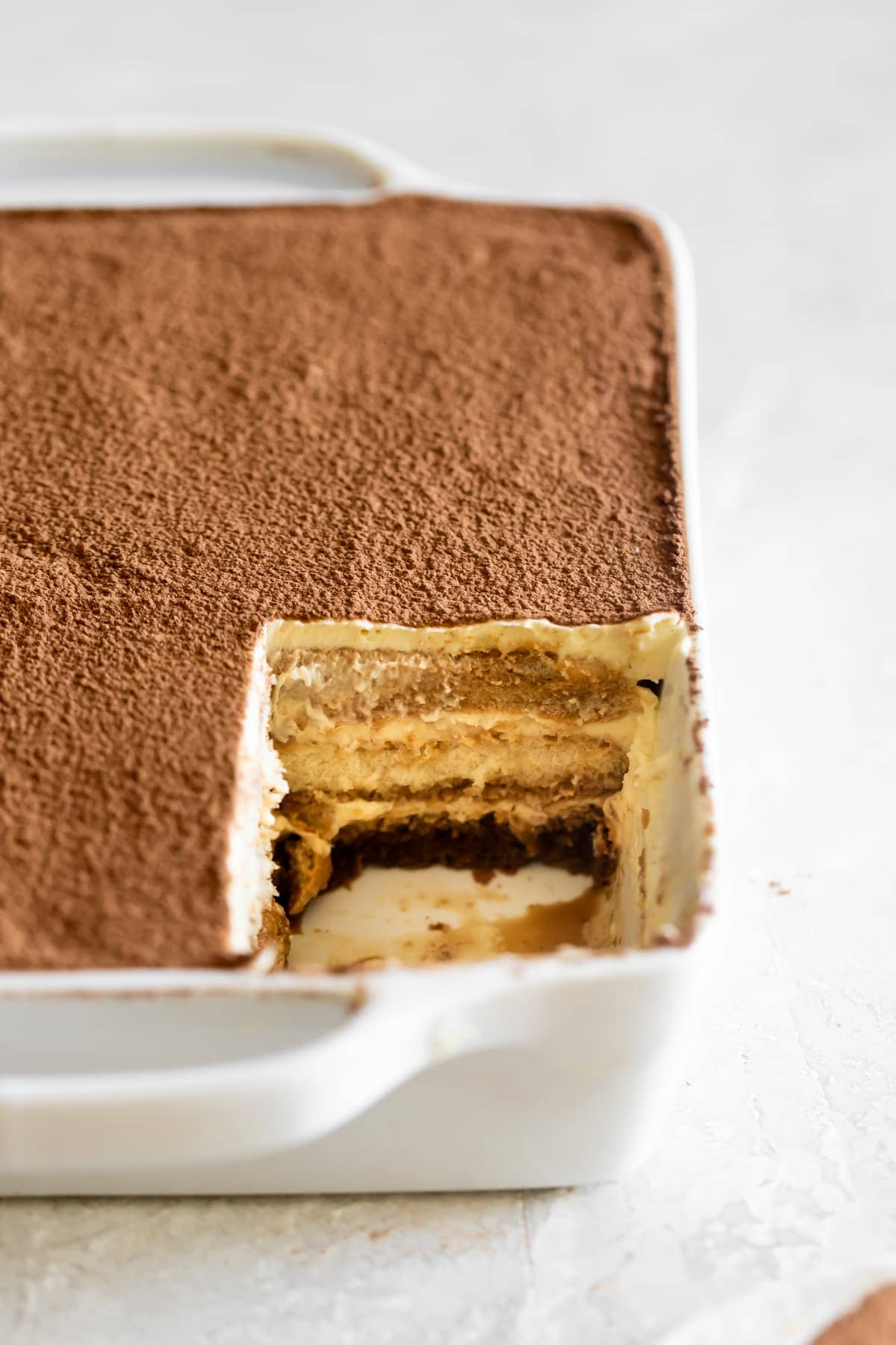 tiramisu with a slice removed to see the filling and layers of mascarpone and espresso soaked ladyfingers