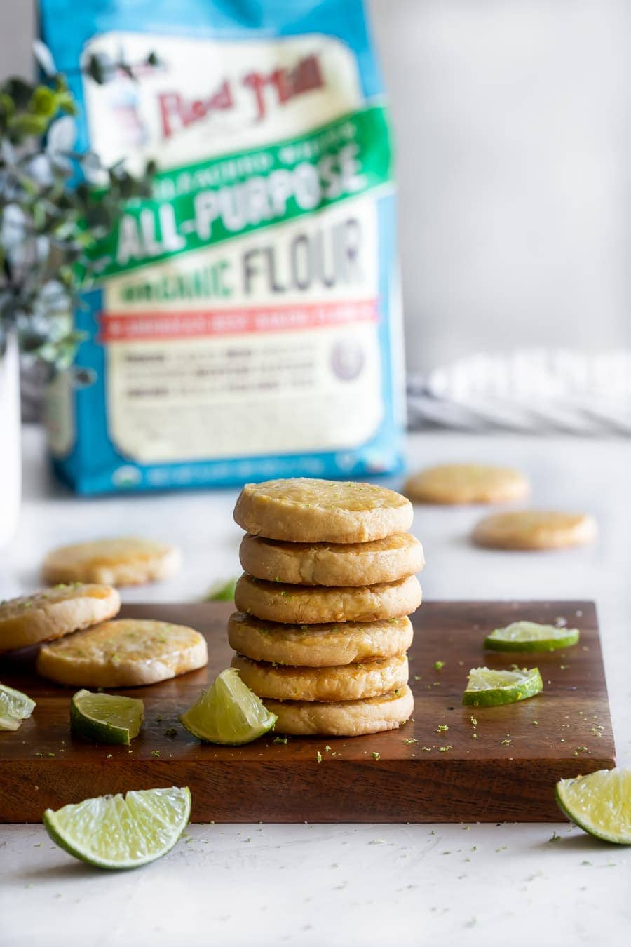 a stack of the best shortbread cookies on a wood cutting board with lime slices