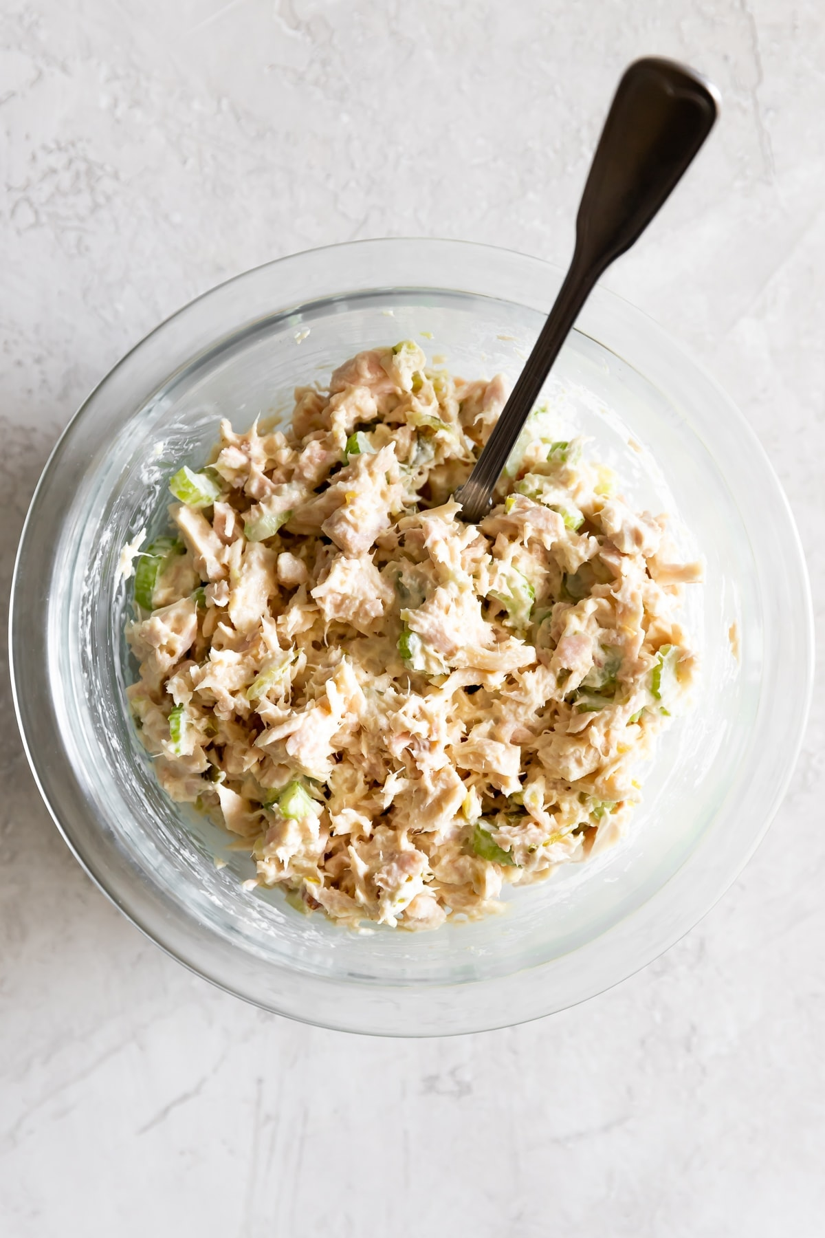 tuna salad mixed with all the ingredients in a clear bowl